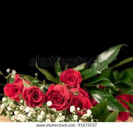Closeup of red roses with green and white flowers for valentines day on a black background - stock photo
