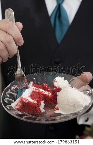 closeup of red velvet cake, hand, and fork