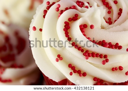 Closeup of red velvet cupcake decorated with swirled icing and sugar beads - stock photo