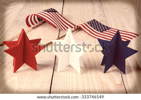Closeup of red, white and blue stars on a wood table with two American flags in the background. Vignette and instagram look applied. - stock photo