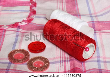 Closeup of red white thread and buttons on a checkered cloth. Sewing accessories. - stock photo