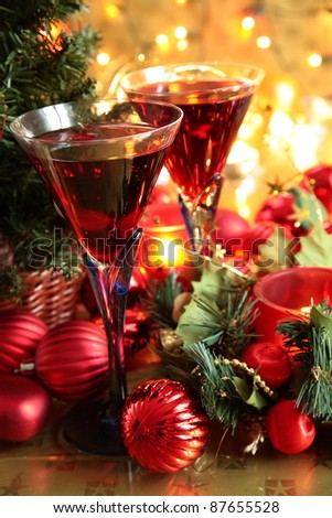 Closeup of red wine in glasses,baubles,candle lights and green twig. - stock photo