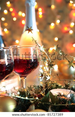 Closeup of red wine in glasses,baubles,green twig,bottle and twinkle lights on golden background.