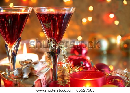 Closeup of red wine in glasses,candle lights, gift box,baubles and twinkle lights on background. - stock photo