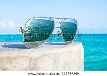 Closeup of reflective sunglasses on wooden post of dock reflecting image of beautiful blue sea on sunny day - stock photo