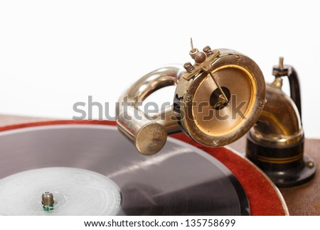 Closeup of retro gramophone with vinyl spinning against white background - stock photo
