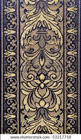 Closeup of retro tapestry fabric pattern with classical floral ornament  in light-yellow and dark-blue tones. - stock photo