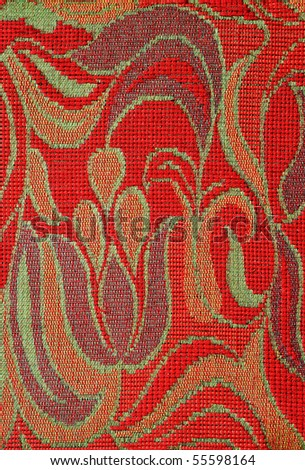 Closeup of retro tapestry fabric pattern with colorful graphical floral ornament on red background. - stock photo