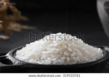 Closeup of rice in wok on black background  - stock photo