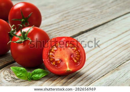 closeup of ripe, juicy cherry tomatoes cut in half with a basil leaf on a wooden table