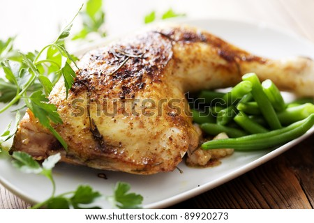 closeup of roast chicken and oven potatoes