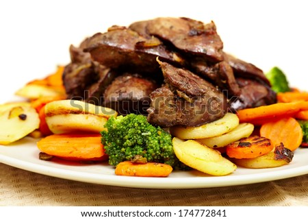 Closeup of roasted chicken liver with fried vegetables isolated on white background - stock photo