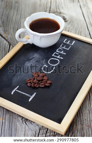 Closeup of roasted coffee beans and cup of espresso on black background, selective focus - stock photo