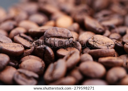 Closeup of roasted coffee beans with focus on one  - stock photo