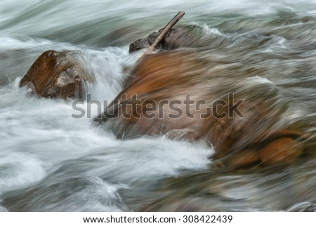 Closeup of rocks in a rapidly flowing western stream. - stock photo