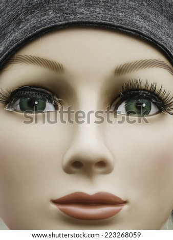 Closeup of round face of expressionless young female mannequin scarecrow with gooey eyes at a fall festival - stock photo