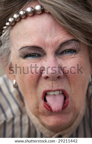 Closeup of rude old woman sticking out her tongue - stock photo