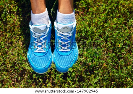 Closeup of running shoes on grass - concept image - stock photo