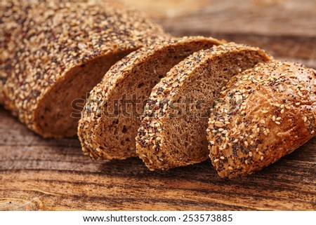 Closeup of rye bread with seeds on a wooden board - stock photo