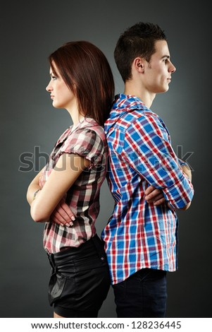 Closeup of sad young couple standing back to back,having relationship difficulties. Gray background - stock photo