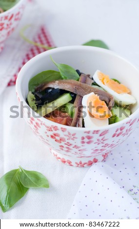 Closeup of salad nicoise with basil and anchovies - stock photo