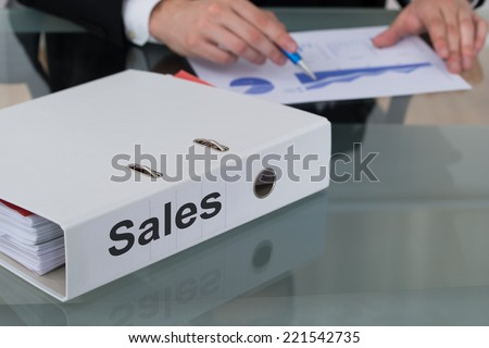 Closeup of sales binder with businessman analyzing graph at desk in office - stock photo