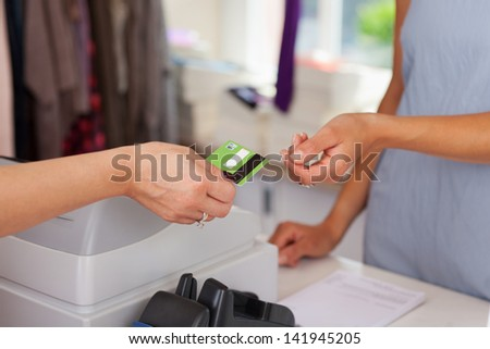 Closeup of saleswoman giving credit card to female customer at boutique counter - stock photo