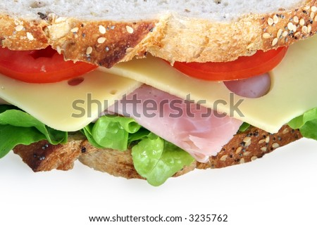 Closeup of sandwich on sourdough wholegrain bread, with ham, curly lettuce, tomato, and jarlsberg cheese.