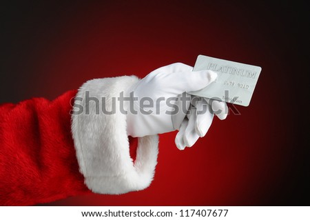 Closeup of Santa Claus hand holding a Platinum Credit Card. Horizontal format over a light to dark red background.