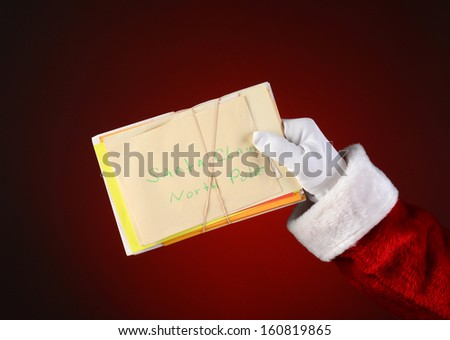 Closeup of Santa Claus holding a bunch of letters bound with a rubber band. Horizontal format on a light to dark red spot background. - stock photo