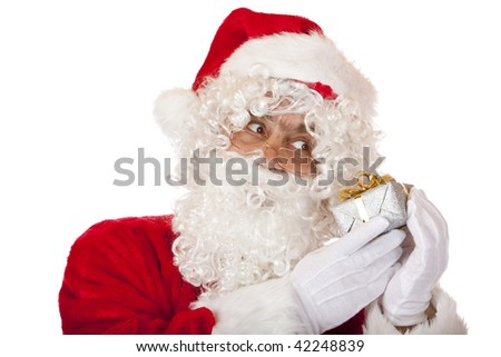 Closeup of Santa Claus holding a Christmas present in his hands and listening it.
