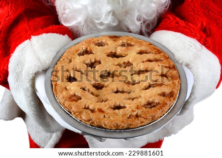 Closeup of Santa Claus holding a fresh baked apple pie in front of his torso. The man is unrecognizable. Horizontal format on a white background. - stock photo