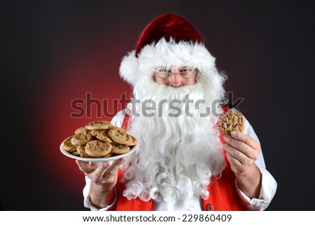 Closeup of Santa Claus holding a plate full of fresh baked Chocolate Chip cookies in one hand and a single cookie in the other. Horizontal format on a red light to dark background.