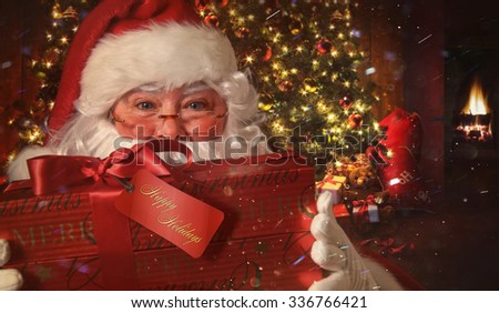 Closeup of Santa Claus holding gift with Christmas scene in background - stock photo