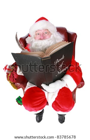 Closeup of Santa Claus (that jolly old elf that  lives at the North Pole) reading and writing in the book of good children, taken with a fish eye lens for added humor - stock photo