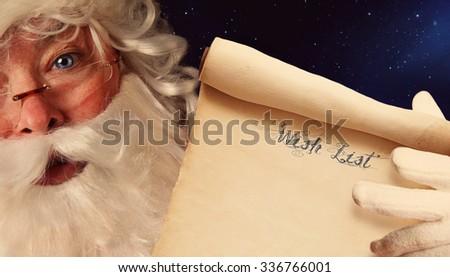 Closeup of Santa Clause holding wish list scroll  - stock photo