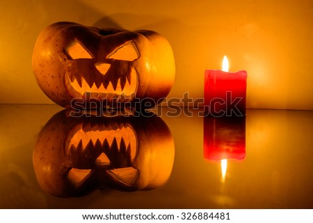 Closeup of scary Halloween pumpkin with candle and reflection. Shallow depth of field - stock photo
