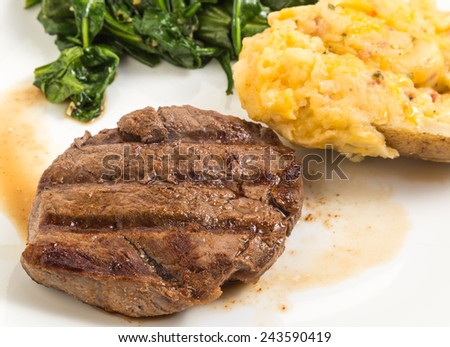 Closeup of seared tenderloin of steak in its juices (au jus) served with stuffed and twice baked potato and wilted spinach. - stock photo