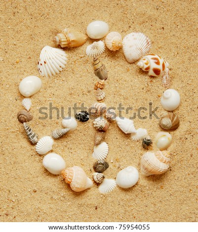closeup of seashells in the shape of a peace sign on a sandy beach - stock photo