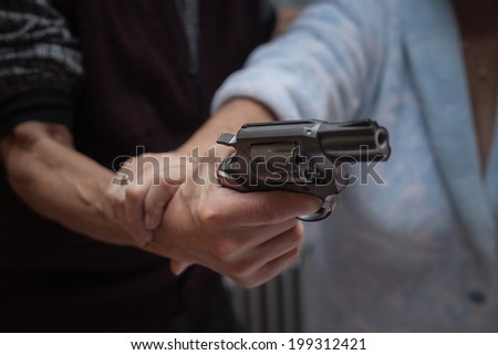 Closeup of senior couple fighting with a gun. - stock photo