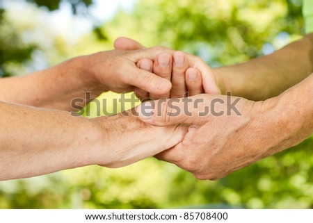 Closeup of senior couple hands holding together outdoors. - stock photo