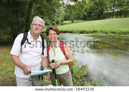 Closeup of senior couple walking by a river - stock photo