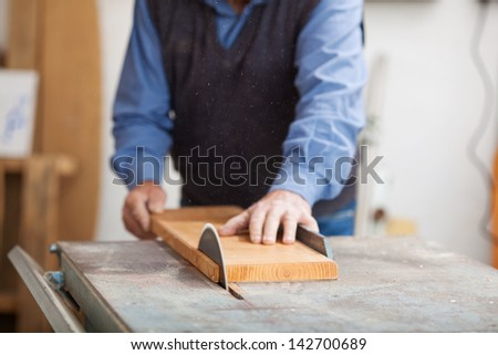 Closeup of senior male carpenter using table saw for cutting wood at workshop - stock photo