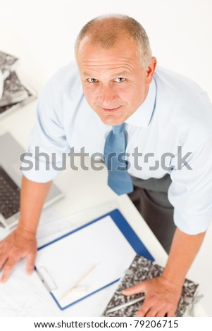 Closeup of senior man working on paperwork at his office table
