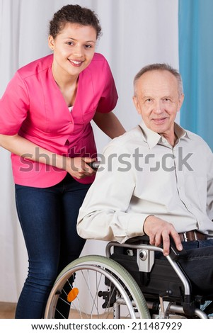 Closeup of senior on wheelchair and nurse - stock photo