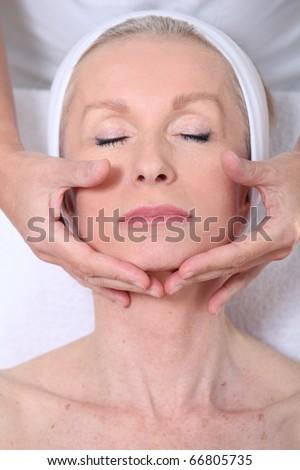 Closeup of senior woman having a face massage - stock photo