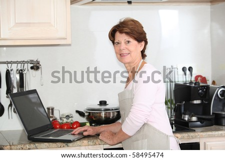 Closeup of senior woman in kitchen with laptop computer - stock photo