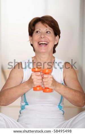Closeup of senior woman lifting weights - stock photo