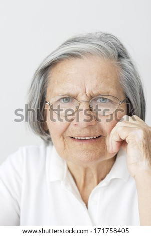 Closeup of senior woman portrait with hand on her chin looking at camera. - stock photo