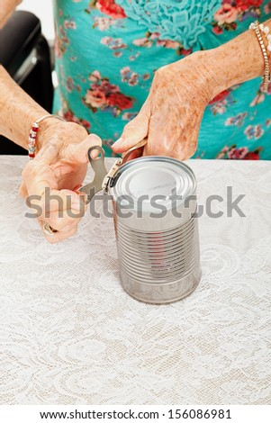 Closeup of senior woman's hands as she struggles to open a can with her painful arthritis.
